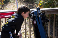 A Cub Scout gets a view of the Sun through a solar telescope at Astronomy Day 2012.