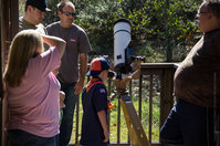 A Cub Scout observes the Sun with Leonard Lynch on Astronomy Day 2012.