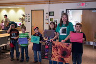 Several children display their sunspot artwork after viewing the sunspots through a telescope while Lora Grosvold encourages them to hold up their drawings.